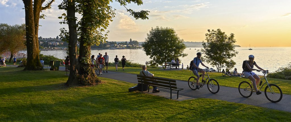 Young couple cycling, others walking or jogging late afternoon and enjoying the sunset